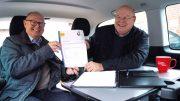 Foto: Jürgen Wille (rechts) unterzeichnet im Energiemobil mit Michael Ibing die Mitgliedschaft im Stadtmarketing.